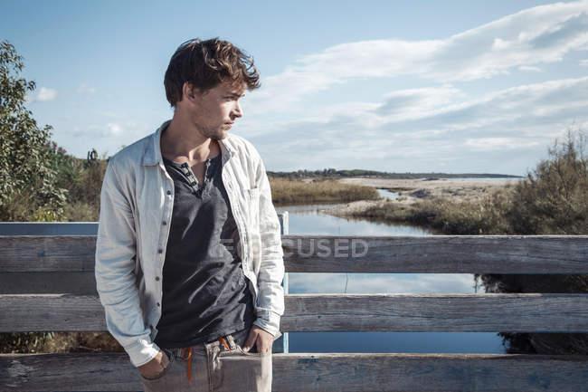 Junger mann lehnt an hölzernen zaun auf brücke über fluss, die hände in taschen wegschauen, costa smeralda, sardinien, italien — Stockfoto