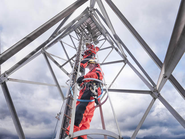 Tower workers climbing radio tower on offshore windfarm, low angle view — Stock Photo