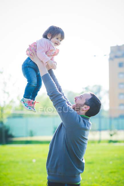 Mann hebt Kleinkind-Tochter im Park auf — Stockfoto