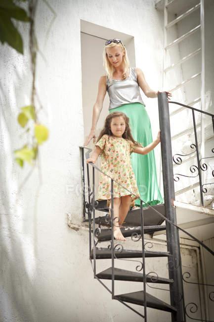 Madre e hija caminando por una escalera de caracol metálica - foto de stock