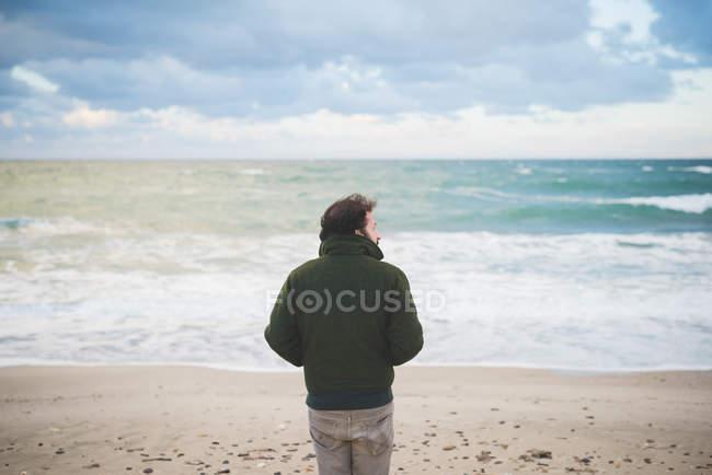 Rear view of man looking sideways on windy beach, Sorso, Sassari, Sardinia, Italy — Stock Photo