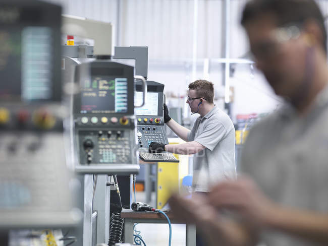 Engineers operating CNC lathes in factory — Stock Photo