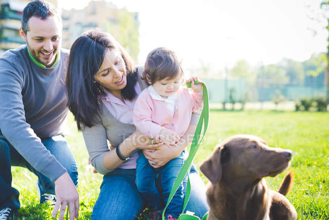 Couple with toddler daughter and dog in park — Stock Photo