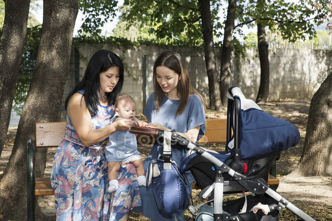 Young woman with mother and baby daughter sitting on park bench — Stock Photo