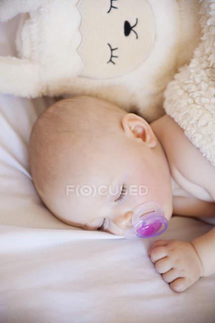 Девочка спит в кроватке с симпатичные игрушки — стоковое фото