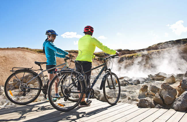 Two female cyclists with hybrid bikes at geothermal site, Krysuvik, Reykjanes, Iceland — Stock Photo