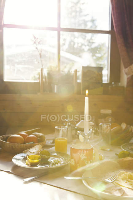 Close up of sunlit breakfast table in log cabin — Stock Photo