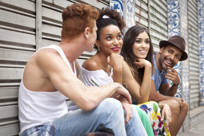 Group of friends sitting together, laughing and smiling — Stock Photo