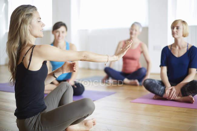 Reife weibliche Tutorin mit ausgestreckten Armen im Pilates-Kurs — Stockfoto