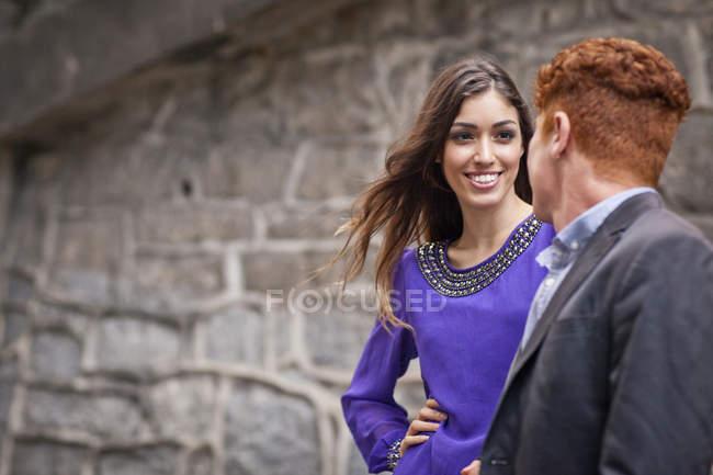Молодая пара стоя вместе, на улице, глядя в сторону, улыбаясь — стоковое фото