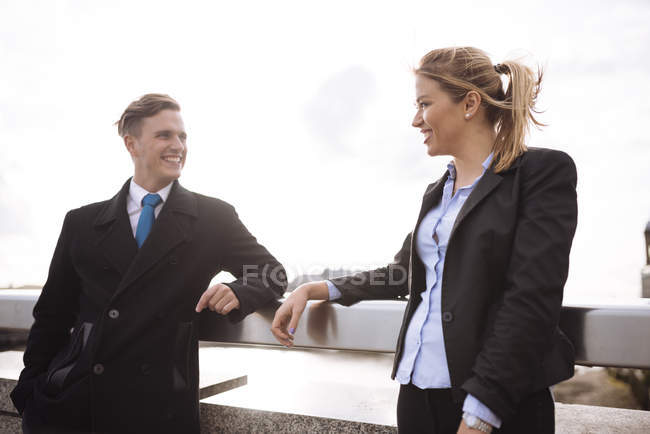 Businessman and businesswoman leaning on rail — Stock Photo