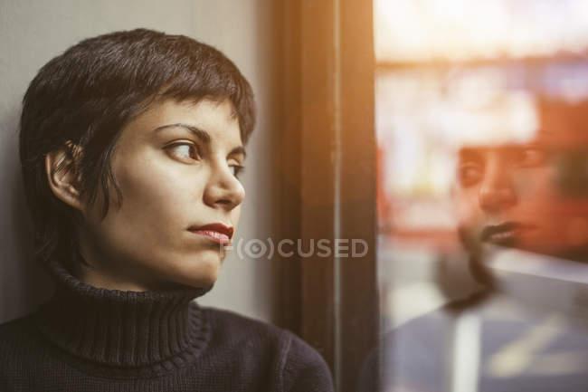 Ritratto di giovane donna che guarda fuori dalla finestra sulla strada — Foto stock