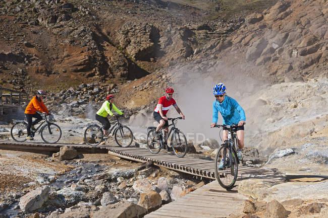 Чотири велосипедисти їзда гібридні велосипеди на геотермальних сайт, Крисувік, Рейкянес, Ісландія — стокове фото