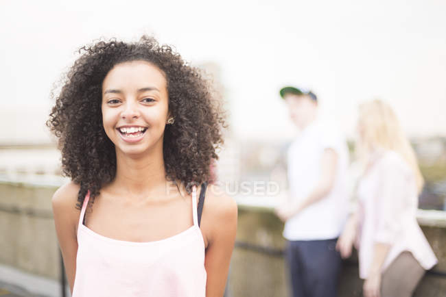 Young woman laughing on city street, people in background — Stock Photo