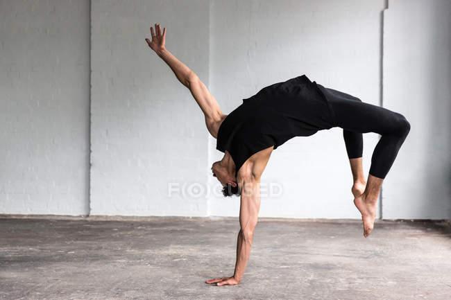 Танцовщица практикуется в студии, наклоняется назад — стоковое фото