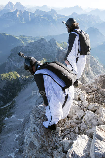 Two male BASE jumpers preparing to launch from mountain, Dolomites, Italy — Stock Photo