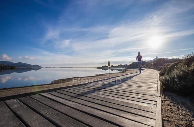 Une coureuse court le long de la promenade de plage, Villasimius, Sardaigne, Italie — Photo de stock