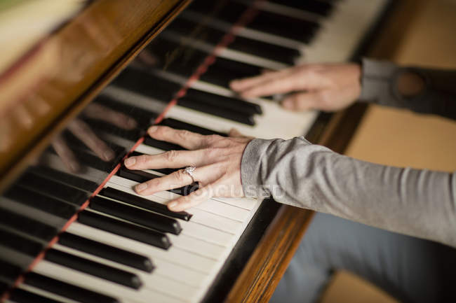Hands of mature woman playing piano — Stock Photo