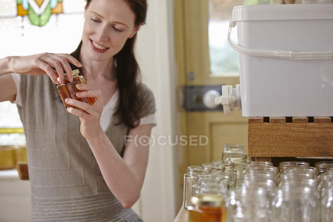 Female beekeeper in kitchen, bottling filtered honey from beehive — Stock Photo