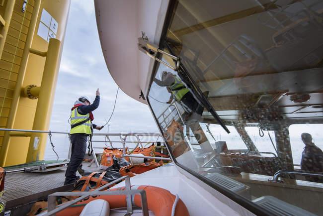 Ingegneri argani parti fino a turbina eolica sul parco eolico offshore — Foto stock