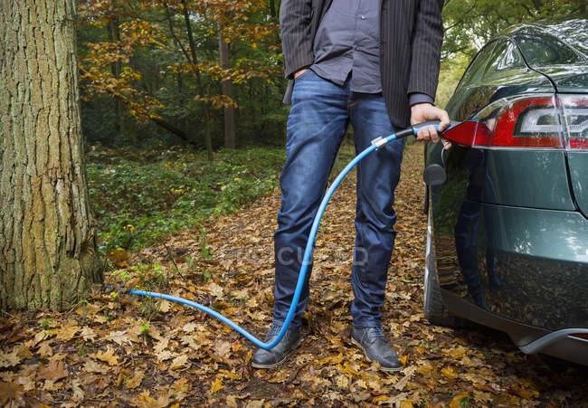 Uomo ricarica auto elettrica nella foresta di autunno — Foto stock