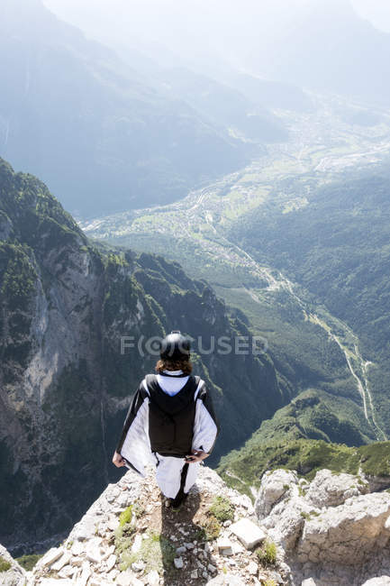 Male BASE jumper in wingsuit standing on edge of mountain, Dolomites, Italy — Stock Photo