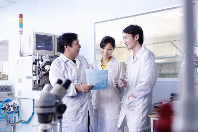 Техніків обговорюючи документ у світлодіодне заводі в Гуандуні, Китай — стокове фото