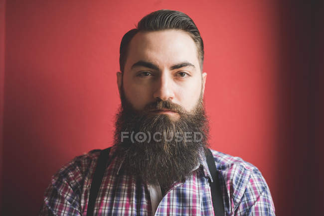 Retrato de joven hombre barbudo, rojo fondo - foto de stock