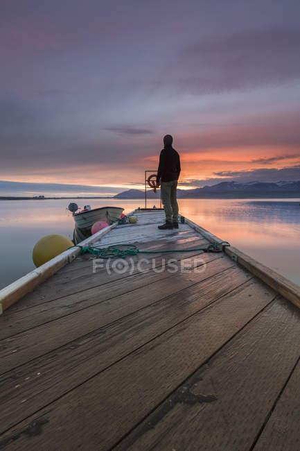 Mann schaut von Pier bei Sonnenuntergang, Hvalfjordur, Island — Stockfoto