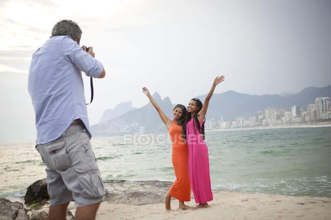 Vista traseira do homem fotografando duas mulheres na praia de Ipanema, Rio De Janeiro, Brasil — Fotografia de Stock
