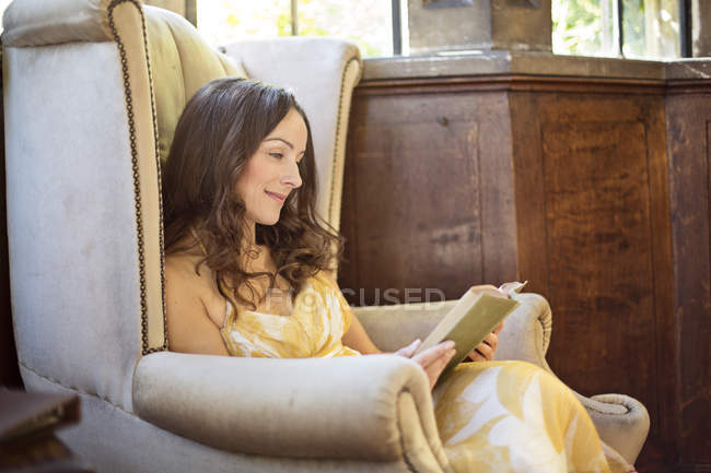 Woman reading book in old armchair at Thornbury Castle, South Gloucestershire, UK — Stock Photo