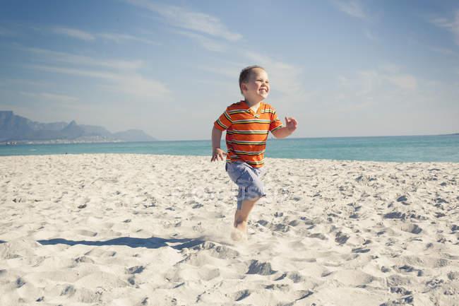 Мальчик бегает по пляжу, Кейптаун, Западный Кейп, Южная Африка — стоковое фото