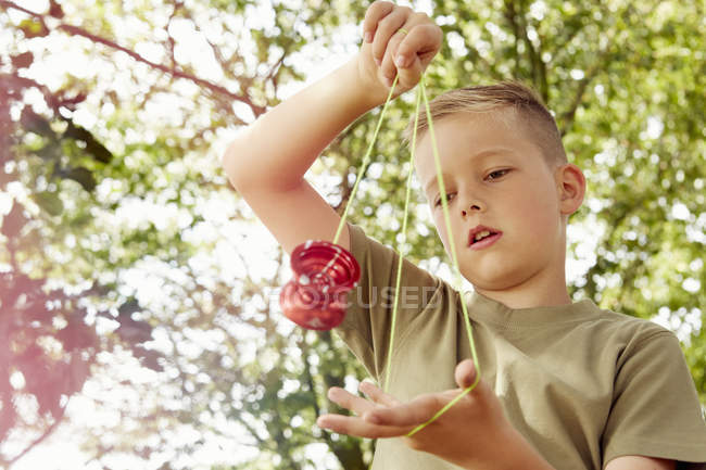 Low angle view of boy playing with yo-yo looking down — Stock Photo