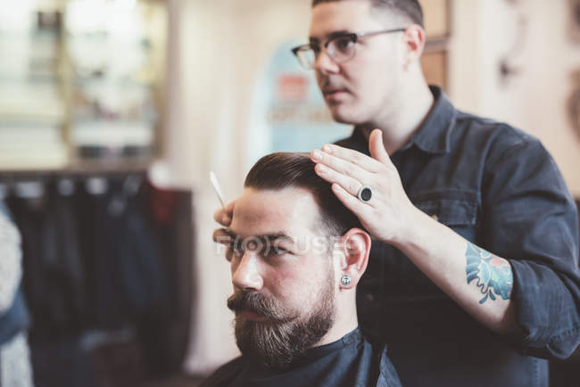 Barber styling client hair in barber shop — Stock Photo