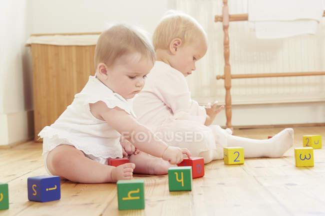 Дитина сестри грають на підлозі з будівельними блоками — стокове фото