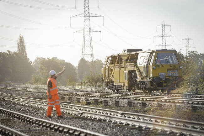 Rail worker signalling to maintenance train on railway in Loughborough, England, UK — Foto stock
