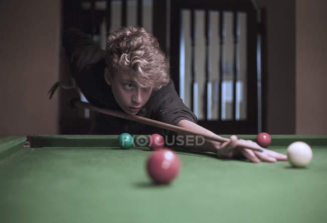 Teenage boy playing snooker indooors — Stock Photo