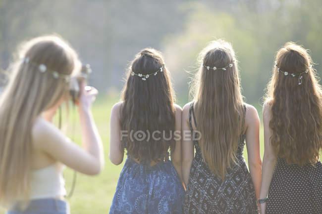 Vista posteriore della ragazza adolescente che fotografa gli amici indossando copricapi a catena margherita nel parco — Foto stock