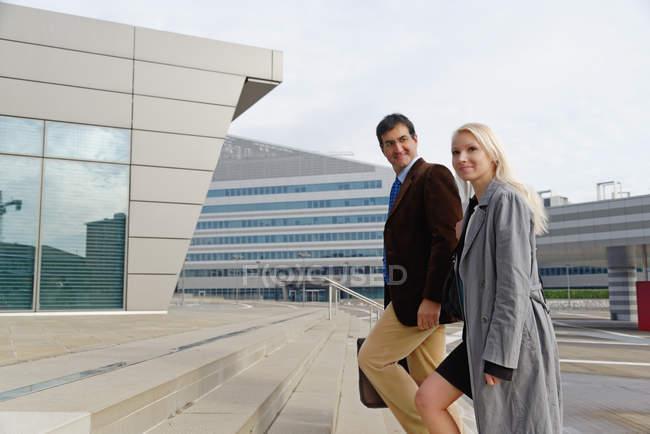 Бізнесмен і бізнесменка піднімаються сходами. — стокове фото