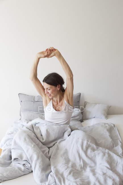Зрелая женщина в жилете сидит в постели под одеялом руки подняты растягивая — стоковое фото