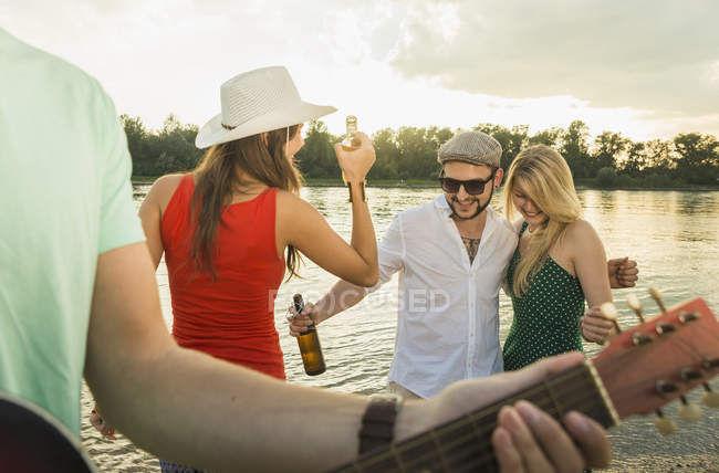 Group of friends with beer, guitar in foreground — Stock Photo