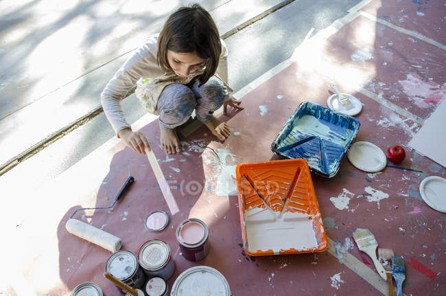 Girl in garage stirring paint in paint tins — стокове фото