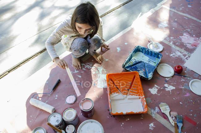 Дівчина в гараж перемішування фарби в фарбу банки — стокове фото