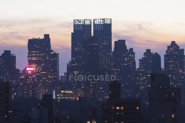 Silhouetted cityscape with buildings illuminated at night, New York City, USA — Stock Photo