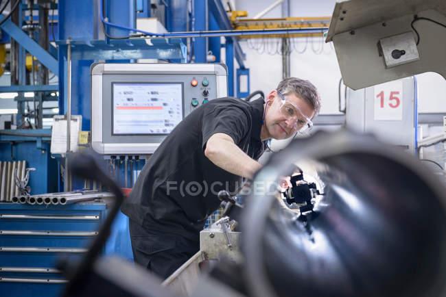 Инженер проверяет режущий инструмент в стальных трубах на заводе — стоковое фото