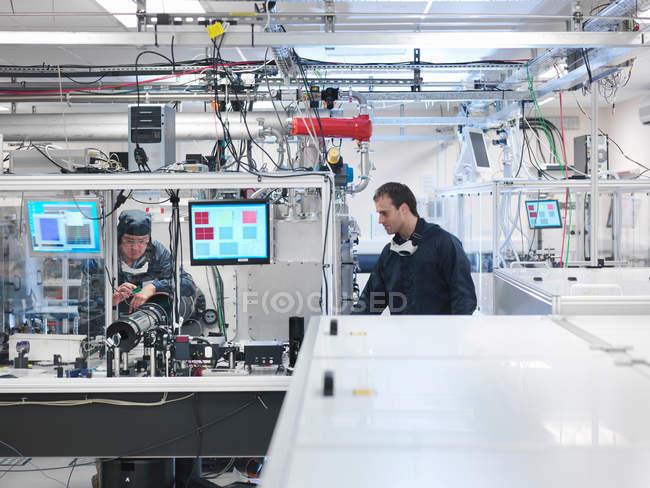 Ученые в защитной одежде, работающие с лазером в лаборатории — стоковое фото