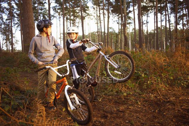 Irmãos gêmeos segurando bicicletas BMX conversando na floresta — Fotografia de Stock