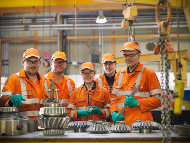 Group of apprentice engineers and engineer inspecting gears — Stock Photo