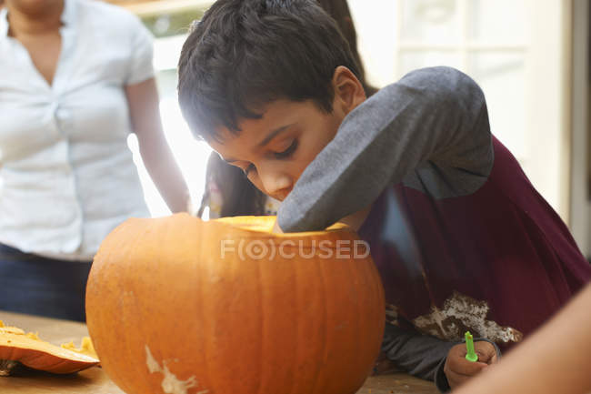 Mother and boy hollowing out pumpkin in dining room — Stock Photo
