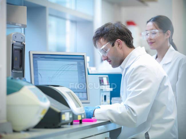 Los científicos que llevan a cabo el proceso de reacción en cadena de la polimerasa (PCR) para amplificar el ADN mediante el uso de un termociclador para crear muestras - foto de stock